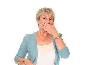 older woman covering her mouth