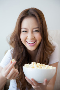 smiling girl eating popcorn